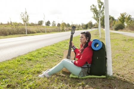Hitchhiker with guitar sitting on the roadside Stock Photo - 15782070