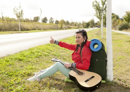 Hitchhiker on the roadside shows thumb up photo