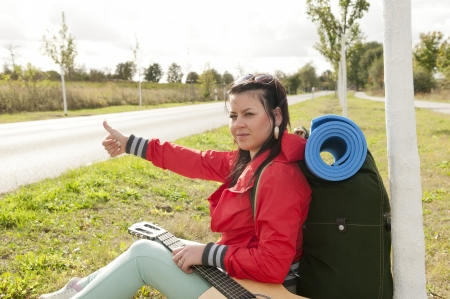 Hitchhiker on the roadside shows thumb up Stock Photo - 15782063