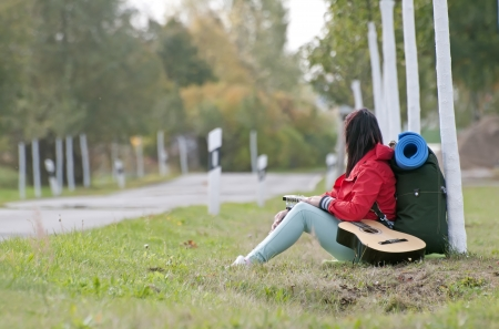 Hitchhiker with guitar sitting on the roadside Stock Photo - 15782056