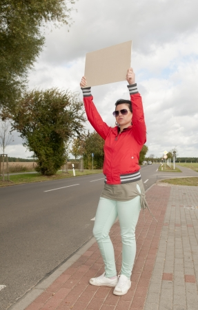 Hitchhiker with blank sign on the roadside Stock Photo - 15782041