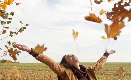 throw up: cheerful young woman throws with leaves Stock Photo