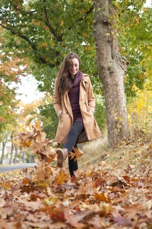 young leaf:  happy young woman walks in autumn leaves