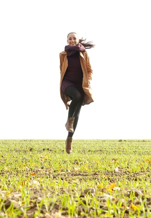 devilment: happy young woman jumping over a field