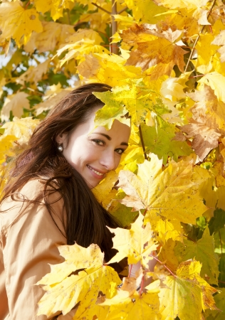 young woman looks through yellow autumn leaves Stock Photo - 16588584