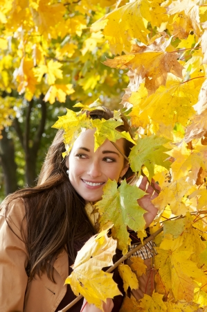 young woman looks through yellow autumn leaves Stock Photo - 16588590
