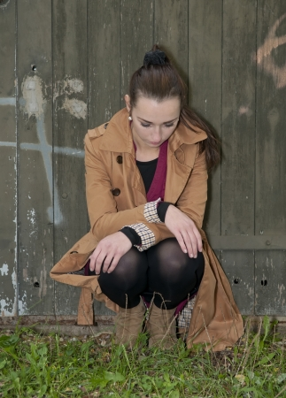 lovesickness: depressed young woman sitting on a woodshed