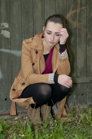 woodshed: depressed young woman sitting on a woodshed