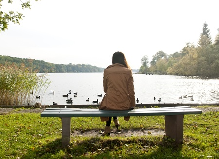 sad lonely: lonely young woman on lake, rear view Stock Photo