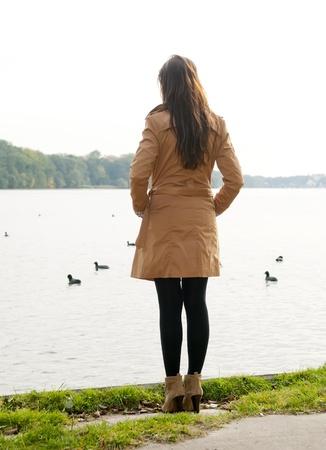 verdrietig meisje: eenzame jonge vrouw op het meer, achteraanzicht
