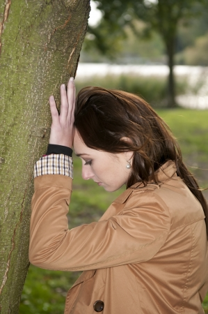 sad young woman leaning against a tree