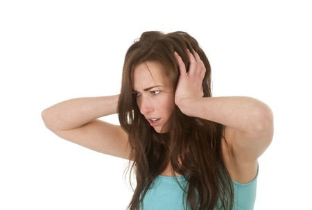 irritable:  pretty young woman holding her ears Stock Photo