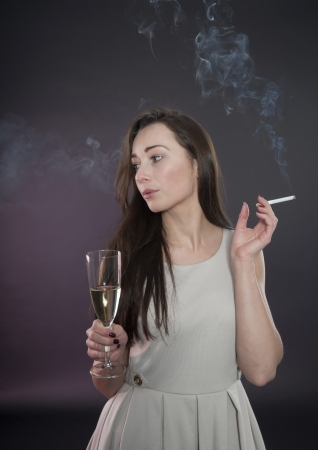 women smoking: young woman with cigarette and champagne Stock Photo