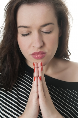 young woman praying, closed eyes photo