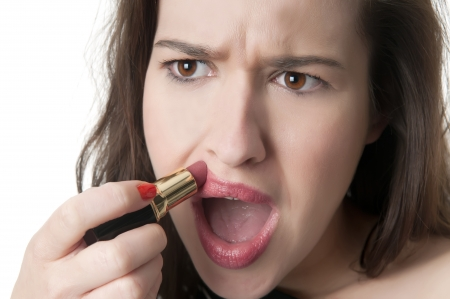 mishap: clumsy young woman applying red lipstick Stock Photo