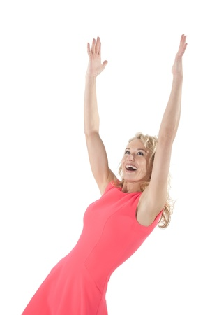 happy young woman in red dress cheering with raised arms photo