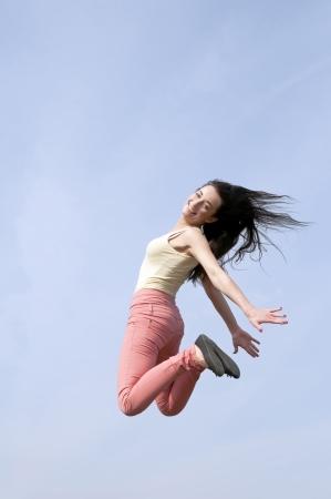 high spirited: happy smiling woman doing joyful leap
