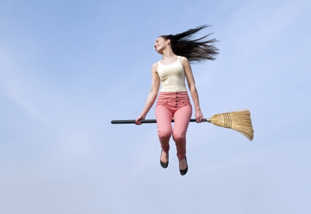 wafting:  happy young woman flying with a broom Stock Photo