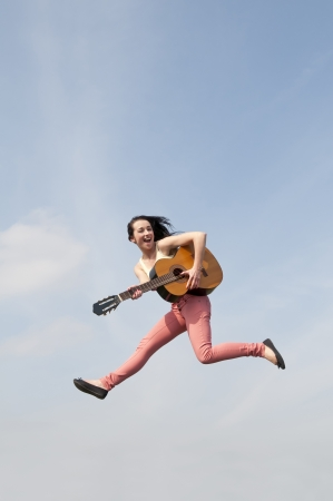 happy young woman jumping with guitar photo