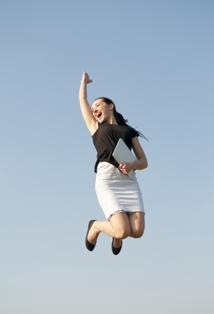happy business woman jumping with digital tablet