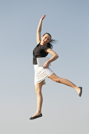 happy business woman jumping with digital tablet photo
