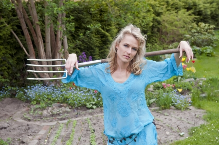 lascivious: graceful young woman with pitchfork in the garden