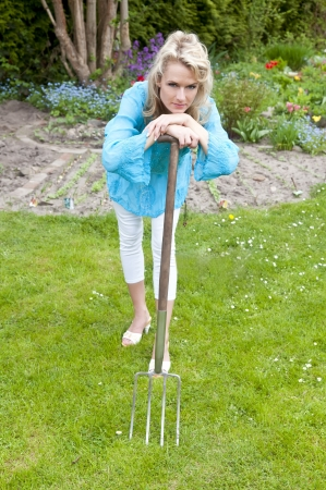 pretty young woman with pitchfork in the garden photo
