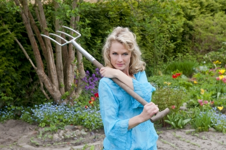 dreamy young woman with pitchfork in the garden Stock Photo