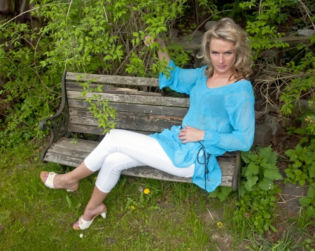 pretty young woman sitting on a wooden bench photo