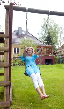 happy young blond woman swinging photo