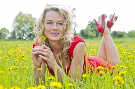 beautiful young woman lying on a meadow photo
