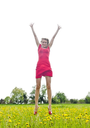 joyful leap, happy young woman jumping on a meadow photo