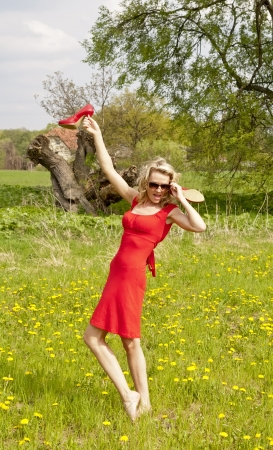 pretty young woman with high heels on a meadow photo
