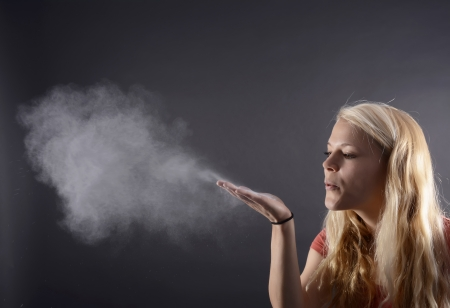 blowing wind: young blond woman blowing powder