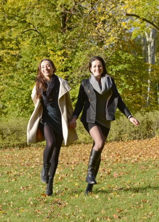 happy sisters running in autumn park photo