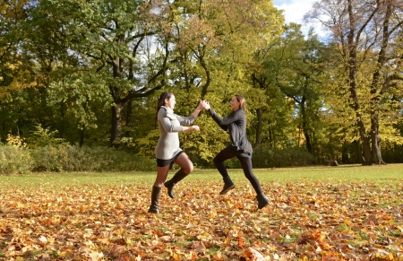 pretty young women dancing in autumn park photo