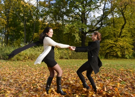 happy young women dancing in autumn park photo