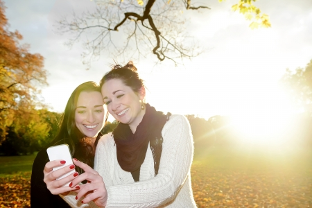laughing girlfriends with smartphone  in autumn park photo