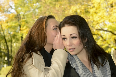 confiding: beautiful girlfriends whispering in autumn park
