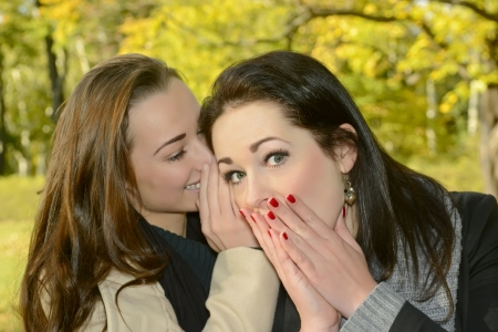 confiding: beautiful sisters whispering in autumn park Stock Photo