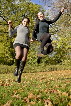 snappy:  laughing sisters jumping in autumn park