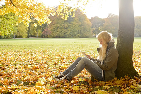 young woman with digital tablet in autumn park photo