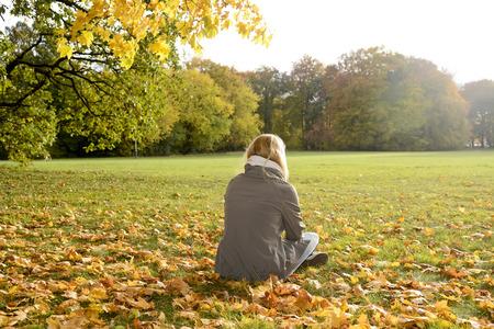 giovane donna: solitario giovane donna seduta in autunno parco, vista posteriore Archivio Fotografico