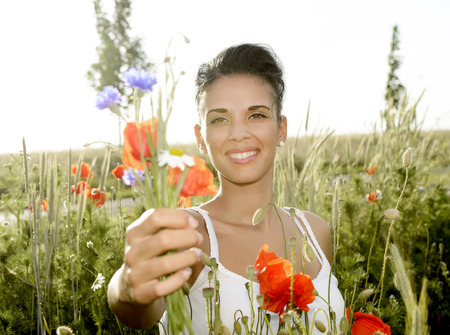 happy young  woman with bouquet in poppy field photo