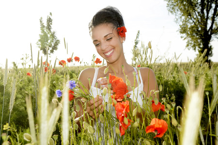 laughing young  woman with bouquet in poppy field photo