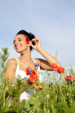 cheerful young  woman with bouquet in poppy field photo