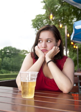 saddened: depressed young woman with beer