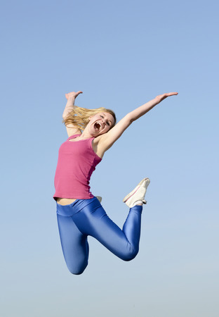 high spirited: joyful young blond woman leaping