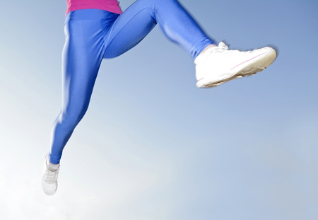 woman legs jogging, blue background photo
