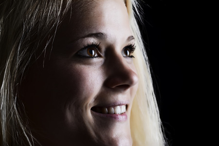 laughing  young blond woman against black background photo